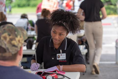 Student nurse works with a client at Giving HOPE community event.